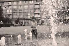 Toddler walking in a splashing water fountain Stock Photo