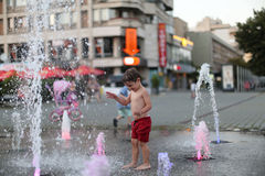 Toddler walking in a splashing water fountain Royalty Free Stock Photo