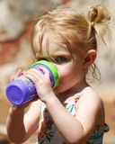A Toddler Warily Sips stock image
