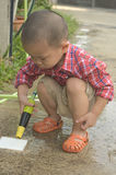 Toddler wash dirt out of ground Stock Image