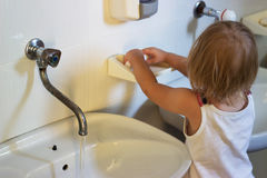 Toddler washing her hands in kindergarden royalty free stock images