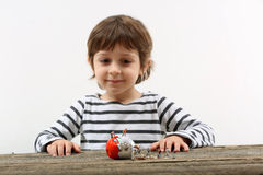 Toddler watching miniature people breaking an egg Royalty Free Stock Photo