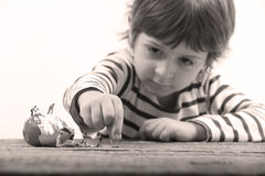 Toddler watching miniature people cracking an egg Stock Photo