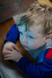 Toddler watching tv. Young blond boy with serious expression watching the television royalty free stock photography