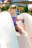 Toddler on the water slide. Cute toddler on the water slide in aqua park Stock Images