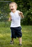 Toddler and water splash Royalty Free Stock Images
