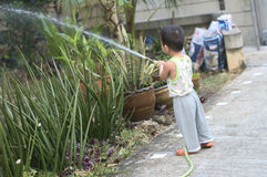 Toddler watering garden Stock Photos