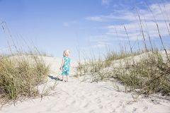 Toddler Wearing Blue Shirt Standing on White Sand Near Green Grass Photo Royalty Free Stock Images