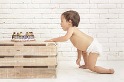 Toddler wearing diapers crawling into his cake. Portrait of toddler wearing diapers crawling into his cake stock image