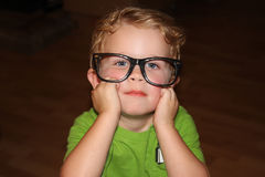Toddler Wearing Glasses. Cute little toddler boy wearing oversized black rimmed glasses in a contemplative pose Stock Photos
