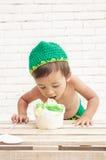 Toddler wearing green hat eating a sponge cake Stock Images