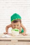 Toddler wearing green hat eating a sponge cake Royalty Free Stock Photography