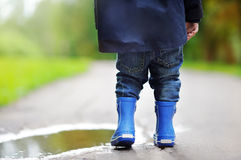 Toddler wearing rain boots standing near a puddle Royalty Free Stock Photo
