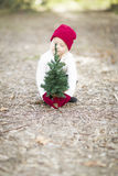 Toddler Wearing Red Mittens and Hat with Small Christmas Tree Stock Photo