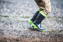 Toddler wearing rubber boots in rainy weather stock photography