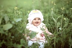 Toddler Wearing Whit Cap on Green Field stock images