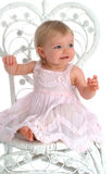 Toddler in Wicker Chair. Toddler girl, smiling, in pink dress, on white background, sitting in wicker chair royalty free stock image