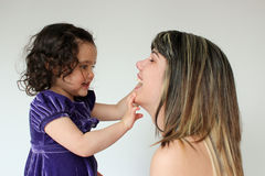 Toddler and woman. Adorable child looking into a woman's mouth Royalty Free Stock Photography