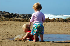 Toddlers on the beach. Little boy and girl playing on the beach Royalty Free Stock Images