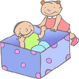 Toddlers with box. Toddlers boy and girl playing with  a box Stock Image