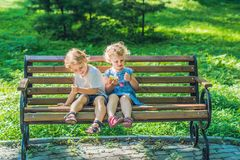 Toddlers boy and girl sitting on a bench by the sea and eat an a royalty free stock image