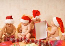 Toddlers in Christmas hats Royalty Free Stock Photos