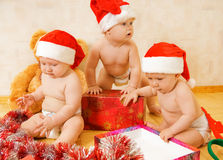 Toddlers in Christmas hats Royalty Free Stock Image