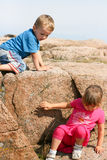 Toddlers Climbing Down a Rock. Young girl and young boy climbing down a large rock in sunny weather Stock Images