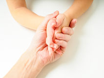 Toddlers hands in fathers hand. Towards, on a white table Royalty Free Stock Photo