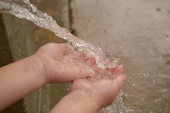 Toddlers hands playing in water from a guttering Royalty Free Stock Photos