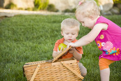 Toddlers Playing with Apple and Picnic Basket. Cute Brother and Sister Toddlers Playing with Apple and Picnic Basket in the Park royalty free stock photos