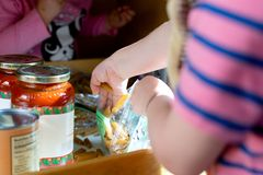 Toddlers playing in the cupboard. Two toddlers playing with pasta and pasta sauce in a kitchen cupboard stock photos