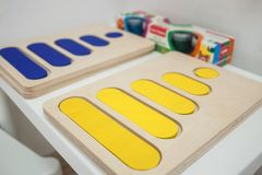 Toddlers playing multicolored educational games, mosaic and puzzles table.  stock photography