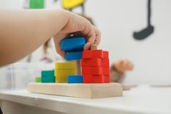 Toddlers playing multicolored educational games, mosaic and puzzles table.  royalty free stock images