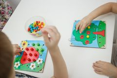 Toddlers playing multicolored educational games, mosaic and puzzles table.  stock images