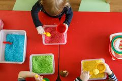 Toddlers playing with sensory box with colourful rice on red table. Top view.  stock image