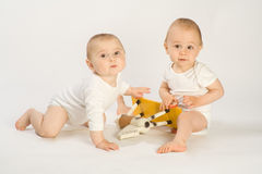 Toddlers and rocking horse Stock Photos