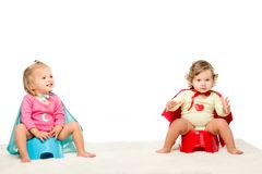 toddlers sitting on potties royalty free stock photo