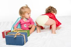 adorable toddlers in superhero capes with wrapped gifts royalty free stock image