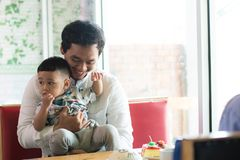 Father and his son playing at cafe in the morning. Todler and father bonding concept stock photography