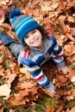 Todler ler i hösten Arkivfoton