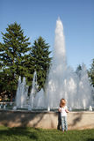 Todler looks a fountain in the summer Royalty Free Stock Photo
