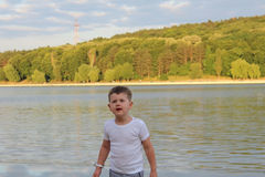 A todler  looks surprised. A todler looks surprised. small boy has fun near the lake at sunny day. expresion of  happiness Royalty Free Stock Photo