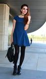 Todo el vestido azul sonriente del lunar de la mujer que lleva que presenta en la calle Imágenes de archivo libres de regalías