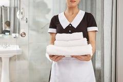 Todo es fresco y limpio Retrato cosechado del housecleaner en el paquete uniforme de la tenencia de la criada de las toallas blan fotografía de archivo