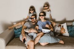 Todo o pai da família com o bebê em seus braços, em mãe e em duas filhas nos vidros especiais olhando a tevê e comendo a pipoca imagem de stock
