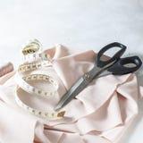 Todo para coser Tela beige, accesorios de costura y tijeras Imagen de archivo