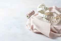 Todo para coser Tela beige, accesorios de costura y tijeras Imagen de archivo libre de regalías