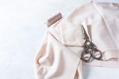 Todo para coser Tela beige, accesorios de costura y tijeras Foto de archivo