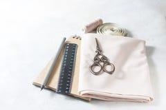 Todo para coser Tela beige, accesorios de costura y tijeras Fotografía de archivo